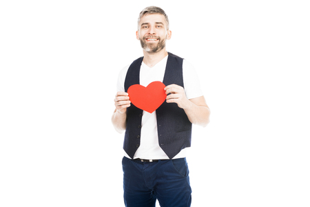 Portrait of young msn holding red heart on white background