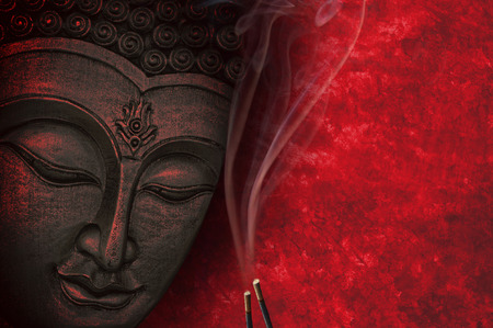 buddha face: Buddha image with red background and incense Stock Photo