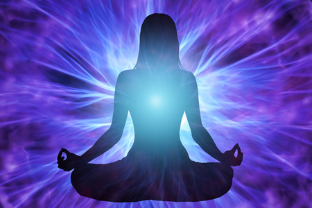 Silhouette of woman meditating with energy beams surrounding him