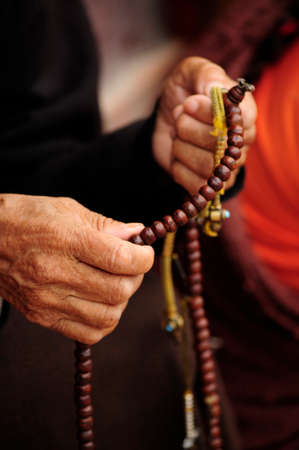 third age: Old hands woman holding a necklace tibetan buddhist Stock Photo