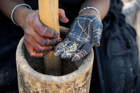 Tattooed hands of Tuareg woman grinding millet