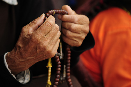 buddhist's: Old hands woman holding a necklace tibetan buddhist Stock Photo