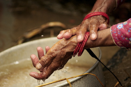 Water cleaning hands of an elderly person