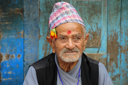 Patan, Nepal. August, 22, 2010 Nepalese elderly man sitting next to his house in Patan