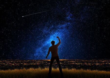 Man in front of the city and the universe with gestures of triumph and success