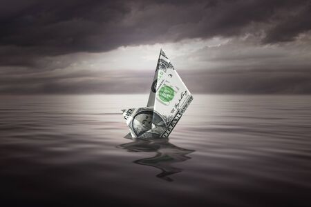 Sinking a little boat made with a dollar bill 写真素材