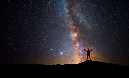 Man in front of the universe with his arms raised
