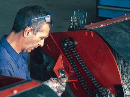 MECHANIC MAKING REPAIRS IN THE WORKSHOP Banco de Imagens