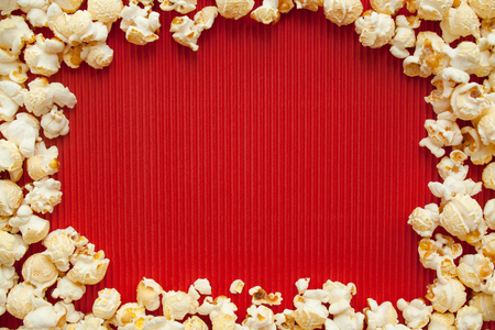 Salty popcorn on red paper background, unhealthy food, movie food Stock Photo