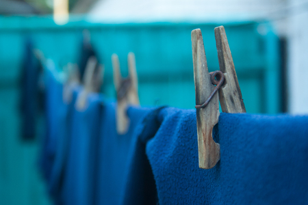 Clothes on old wooden clothespins hanging on a rope Banco de Imagens
