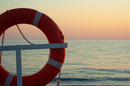 Orange life ring near sea on sunset. Saving life concept