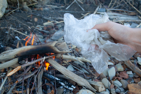 Plastic bag in man's hand near bonfire. Waste incineration concept. Air pollution Stockfoto
