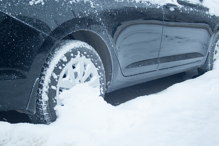 Wheel of black car at snow close up. Winter driving concept