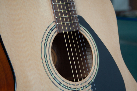 Close up of acoustic guitar with metal strings. Music concept. Hobby, leisure concept. Learn to play the guitar.