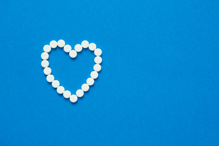 white pills in the shape of a heart are scattered on a blue background. Top view