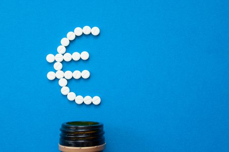 white pills in the shape of a euro are scattered on a blue background next to a dark bottle. Stok Fotoğraf - 121263790