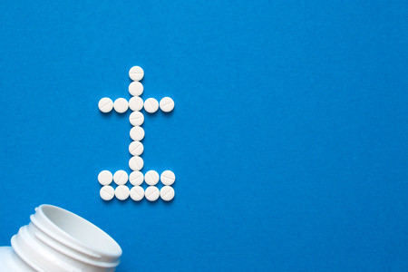 white pills in the shape of a grave cross are scattered on a blue background next to a white bottle. Depression, harm of drugs concepts. Top view with copyspace