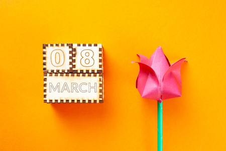 wooden cubes and paper tulip with the inscription March 8 on orange background. 8 march concept