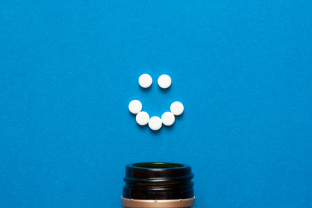 white pills in the shape of a smile are scattered on a blue background next to a dark bottle. Treatment of depression. psychological health concept