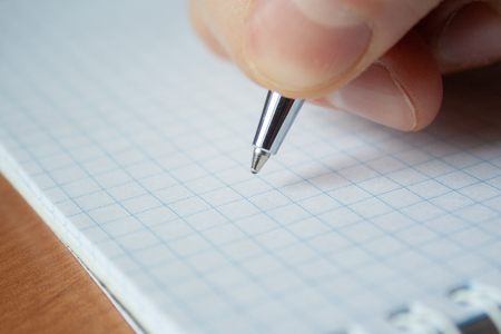 Pen and white notepad paper close up in man's hand