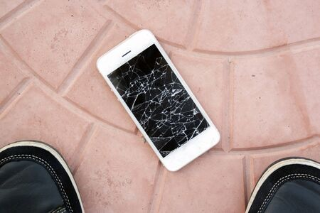 broken smartphone screen. Feet and smartphone with a broken screen on the tile floor. Top view broken phone