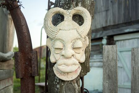Old african ancient handmade mask on wooden fence near house. African culture traditional masks close up 写真素材