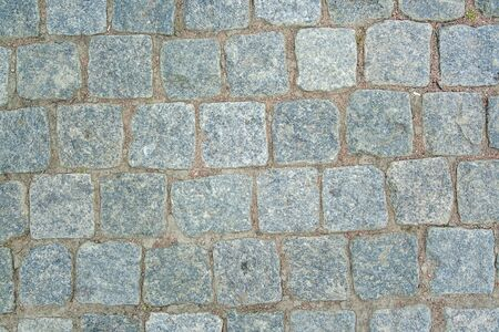 Old aged granite paving stones. Texture of old granite paving stones. The texture of the pavement granite pattern wallpaper for design. Rough texture Foto de archivo
