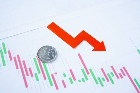 one rouble coin on currency graph with red arrow down. exchange rate chart. ruble depreciation. Exchange rate of rouble fall. Rouble to dollar Archivio Fotografico