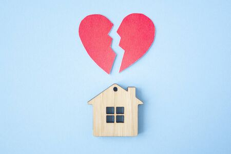 Divorce, division of property, poverty and no money concept. Wooden house with broken heart on bright blue background. Mortgage, rent, realtor Stockfoto