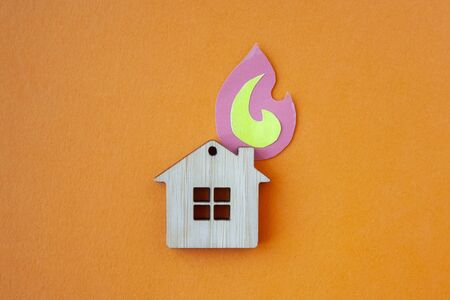 Fire house, insurance and mortgage concept. Small wooden house toy and paper fire shape on orange background top view