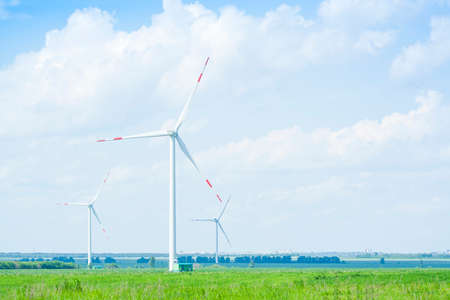 many windmills stand on a large field