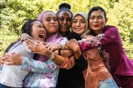 Cinco amigas de diferentes etnias y religiones se abrazan en un abrazo grupal Foto de archivo