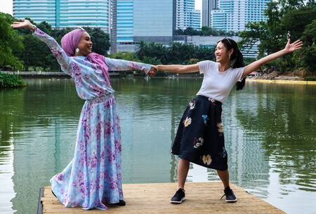 A malay and chinese girl stretch out their arms in celebration of their friendship