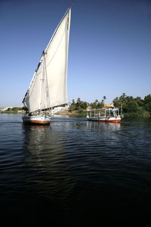 sailer: a sailboat and a motorboat in nile next luxor Stock Photo