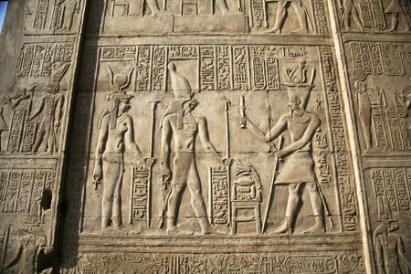 relief on a egyptian wall with a god a pharaoh an his wife photo