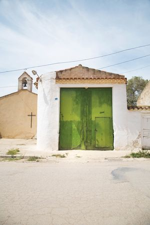 green wooden door and basic church at chinchilla albacete spain photo