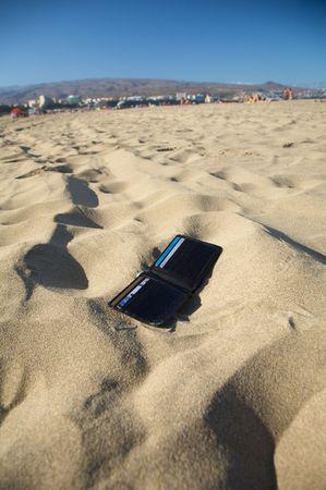 verloren zwart lederen portemonnee met vier kaarten op het strand Stockfoto