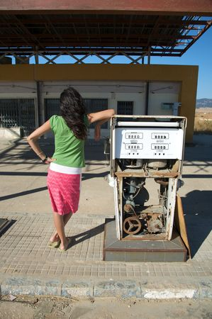 gasoil: back woman lean on an old dilapidated gas pump