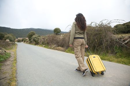 avila: woman with suitcase on rural road at gredos mountains in avila spain