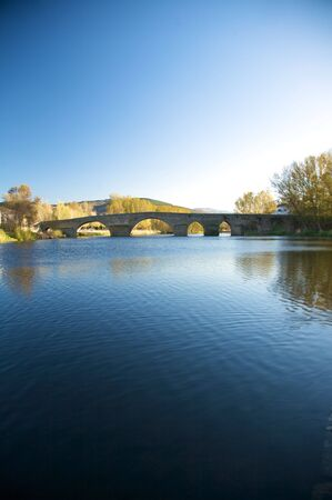 river with bridge at barco village in avila spain photo