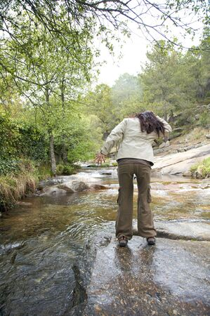 woman next to a river at gredos in avila spain photo