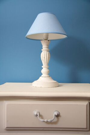 bedside: white bedside table and lamp with blue lampshade