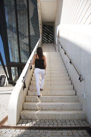upstairs: woman walking upstairs outside the lyon airport Stock Photo