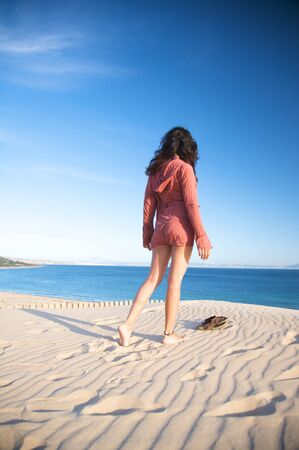 woman at sand dune in spain with african horizon photo