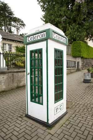irish white and green phone box at the street