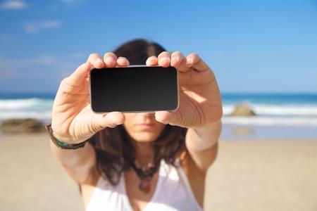 fiestas electronicas: teléfono inteligente en la mano de la mujer en una playa de Asturias España