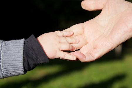 abuelo: anciana y al beb� que toma sus manos sobre fondo verde