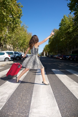 brunette woman with red suitcase walking in Madrid city Spain photo