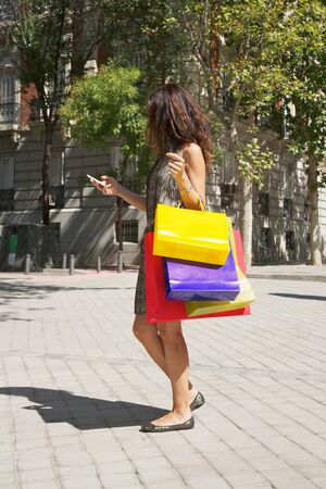 brunette woman with shopping bags walking in Madrid city Spain photo