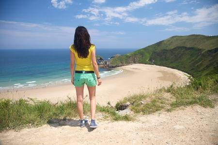 woman back at Torimbia beach in Asturias Spain photo
